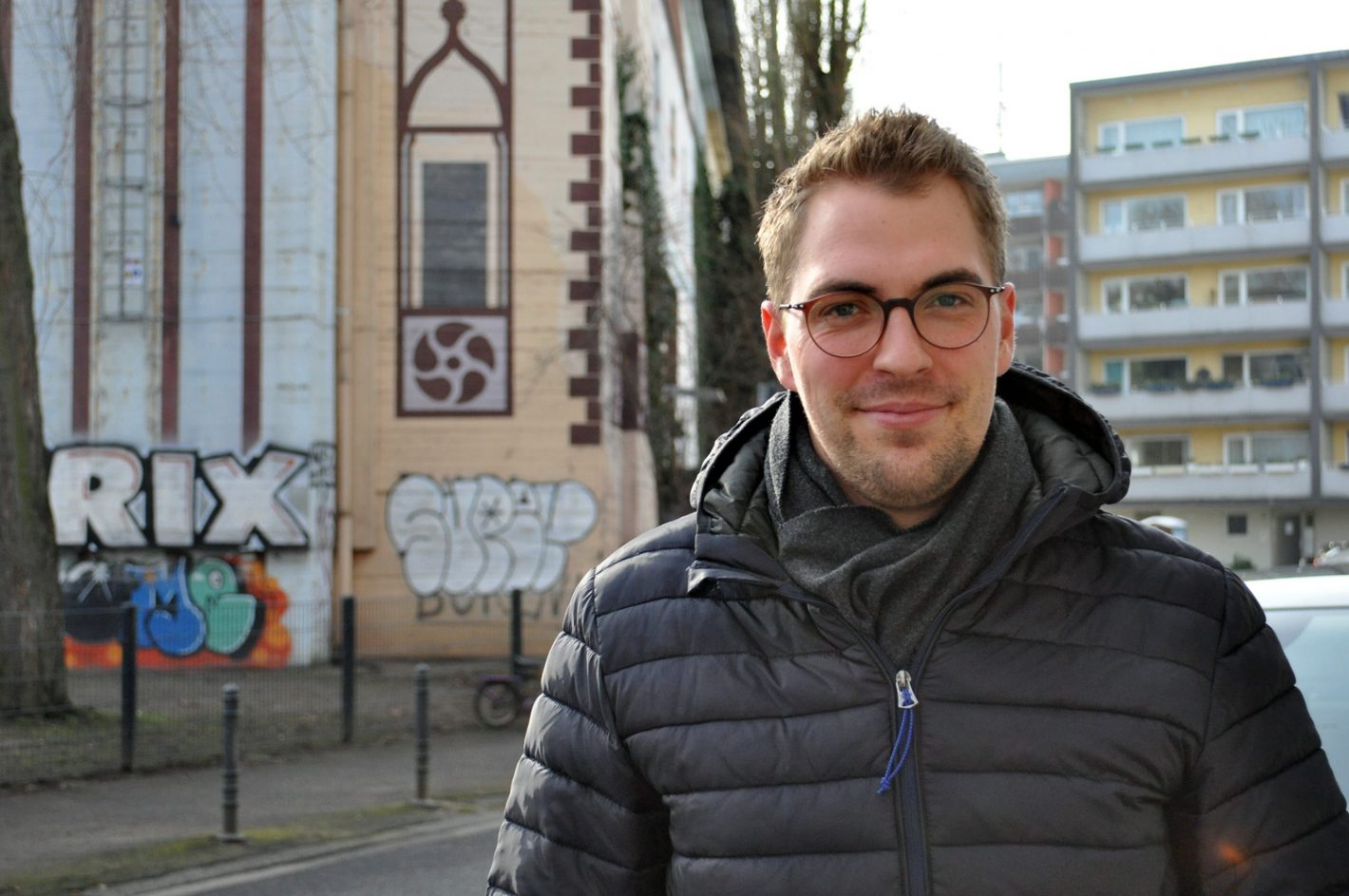 Mann in Winterjacke vor Graffiti