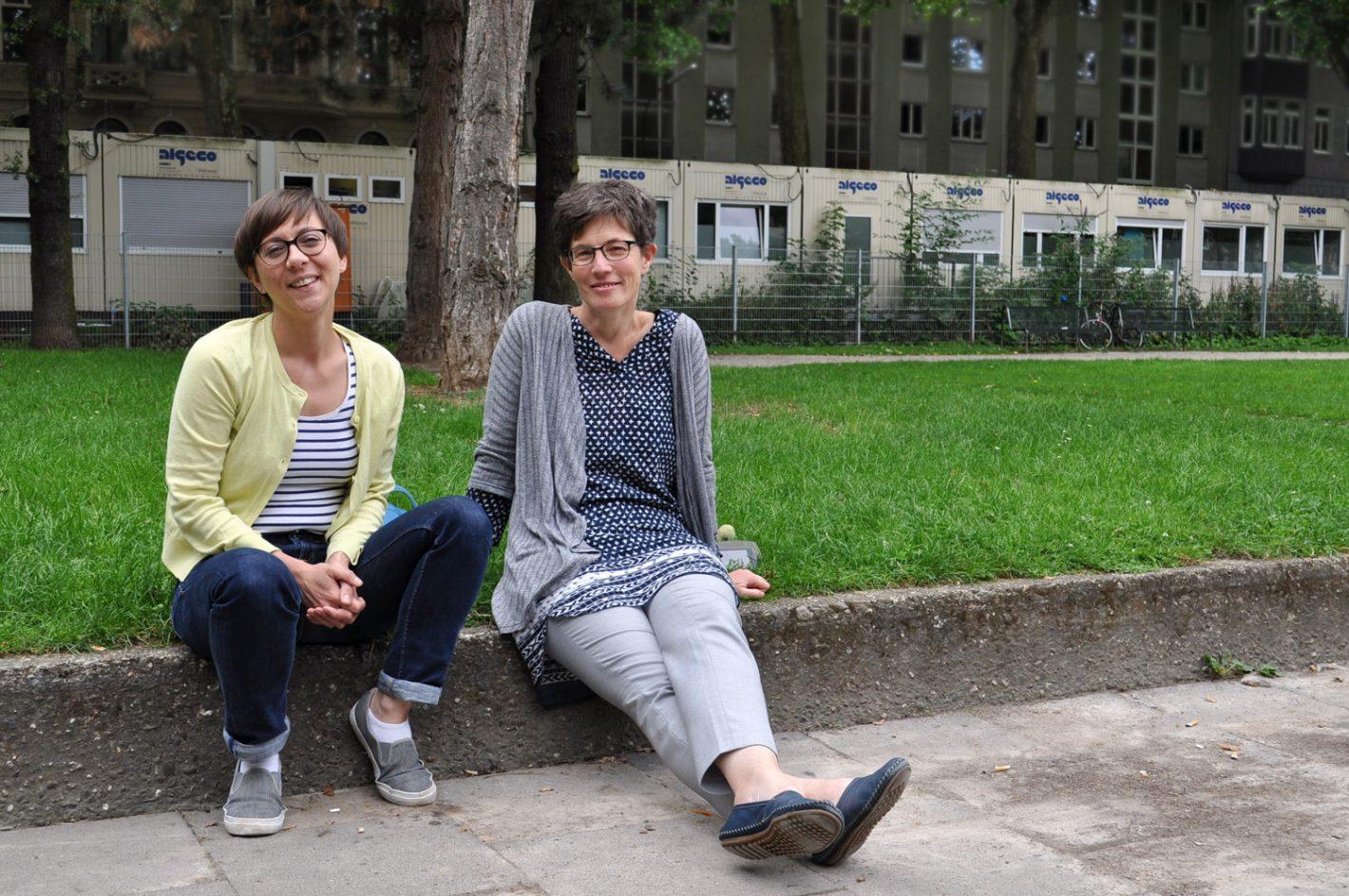 zwei Frauen sitzen auf Mauer an Wiese