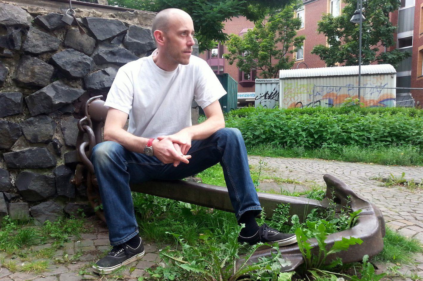 Mann sitzt auf Anker